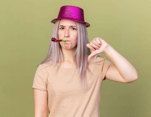 Jeune belle fille mécontente portant un chapeau de fête soufflant un sifflet de fête montrant le pouce vers le bas