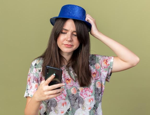 Jeune belle fille mécontente portant un chapeau de fête tenant et regardant le téléphone en mettant la main sur la tête