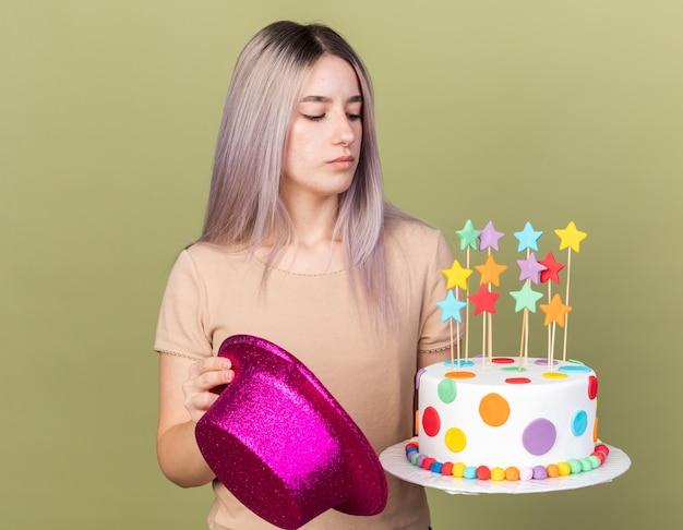 Jeune belle fille mécontente tenant un chapeau de fête regardant un gâteau dans sa main