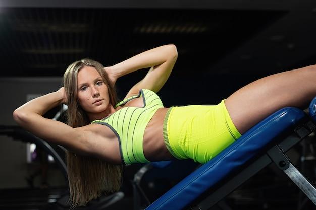 Jeune belle fille musclée entraîne la presse dans la salle de sport