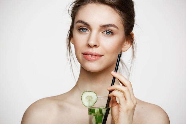 Jeune belle fille nue avec une peau parfaitement propre souriant regardant la caméra tenant un verre d'eau avec des tranches de concombre sur fond blanc. traitement facial.