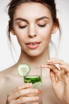 Jeune belle fille nue avec une peau propre parfaite souriant tenant un verre d'eau avec des tranches de concombre sur fond blanc. traitement facial.