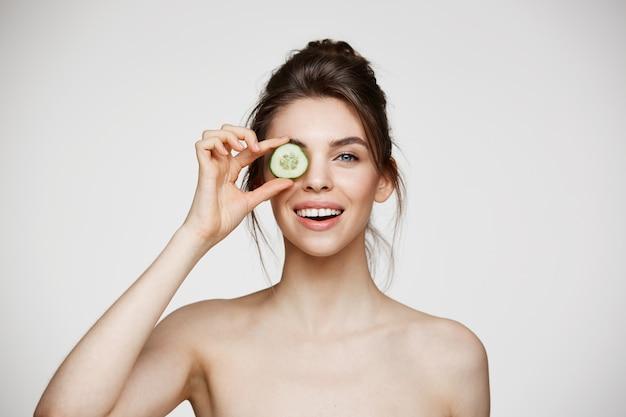 Jeune belle fille nue souriante cachant l'oeil derrière une tranche de concombre regardant la caméra sur fond blanc.