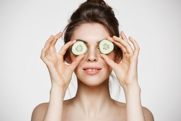 Jeune belle fille nue souriante cachant les yeux derrière des tranches de concombre sur fond blanc. soins de beauté et cosmétologie.