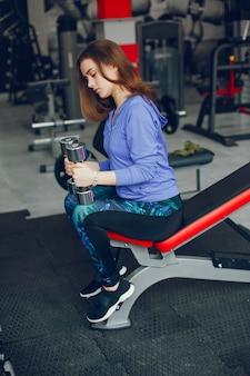 Une jeune et belle fille passe un bon moment à la gym