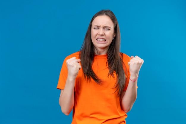 Jeune belle fille portant un t-shirt orange frustré serrant les poings se sentir irrité debout sur fond bleu isolé