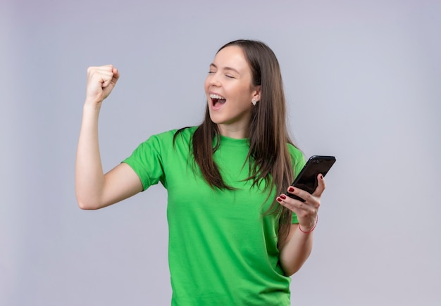 Jeune belle fille portant un t-shirt vert tenant le smartphone levant le poing fermé heureux et sortit souriant se réjouissant de son succès debout sur fond blanc isolé