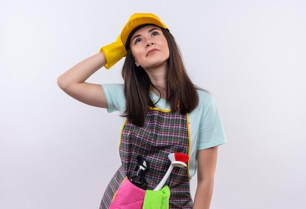 Jeune belle fille portant un tablier, une casquette et des gants en caoutchouc à la recherche avec un look de rêve
