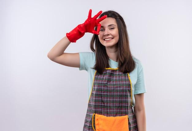 Jeune belle fille portant un tablier, une casquette et des gants en caoutchouc souriant avec un visage heureux faisant signe ok
