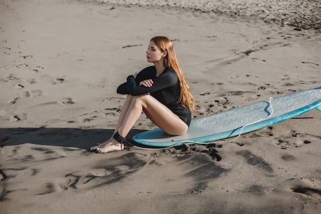Jeune belle fille posant sur la plage avec une planche de surf, surfeuse, vagues de l'océan