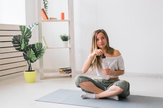 Jeune belle fille pratiquant le yoga au tapis de l'eau potable pendant la pause fitness et mode de vie sain