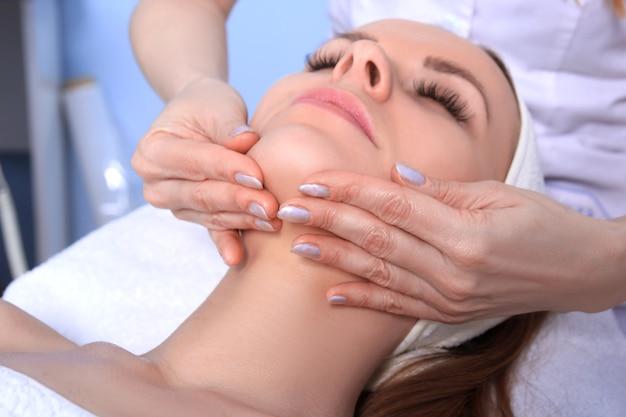 Jeune belle fille recevant des soins de spa. médecin faisant un massage du visage.