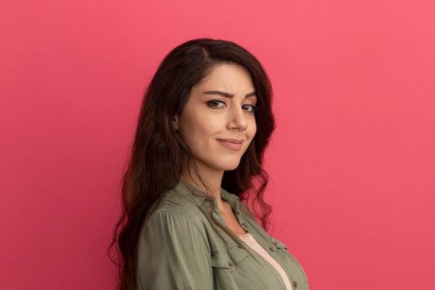 Jeune belle fille regardant l'avant portant un t-shirt vert olive isolé sur un mur rose avec espace copie