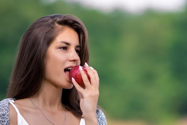 Jeune belle fille en robe blanche mange une pomme biologique mûre.