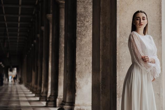 Jeune belle fille en robe de mariée blanche tient la main sur la poitrine
