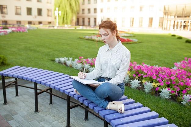 Jeune belle fille rousse avec des taches de rousseur assis sur un banc