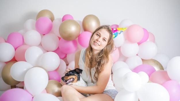Jeune belle fille s'est réveillée entourée de ballons le jour de l'anniversaire avec son chien