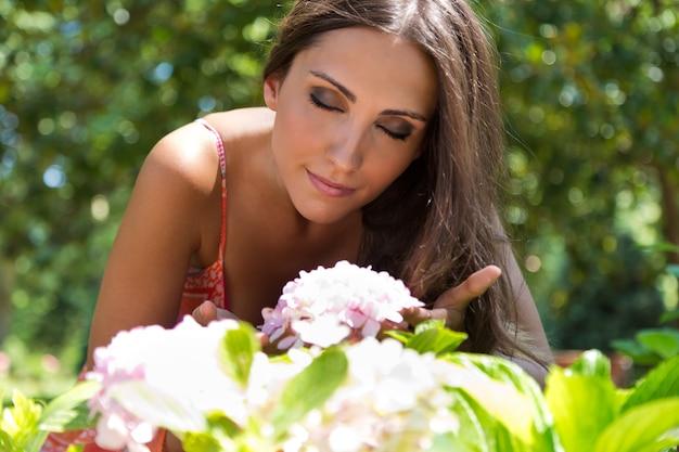 Jeune belle fille sent des fleurs, contre un vert jardin d'été.