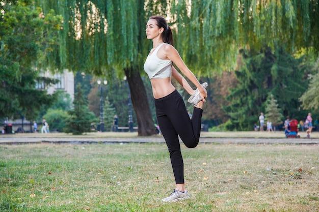 Jeune belle fille sexy heureuse s'étend dans le fond de gens de jardin de parc avec les cheveux noirs