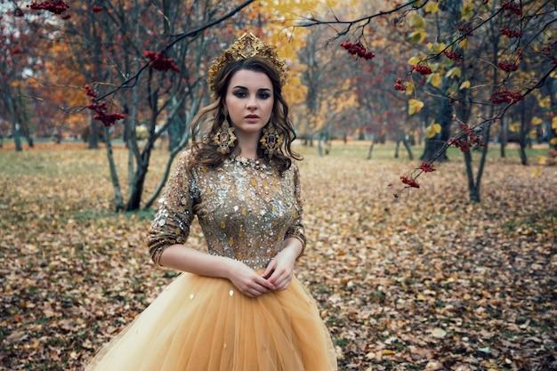 Jeune belle fille sexy en robe d'or dans la forêt d'automne