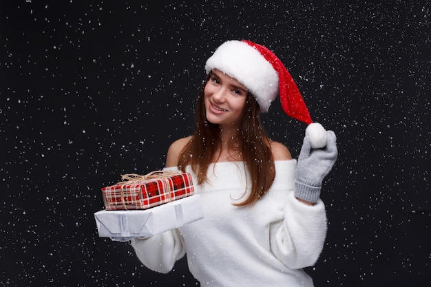 Jeune belle fille souriante au bonnet rouge tenant des boîtes-cadeaux