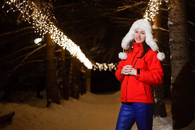 Jeune belle fille souriante heureuse portant un chapeau de fourrure tricotée blanche. modèle posant dans la rue. concept de vacances d'hiver.