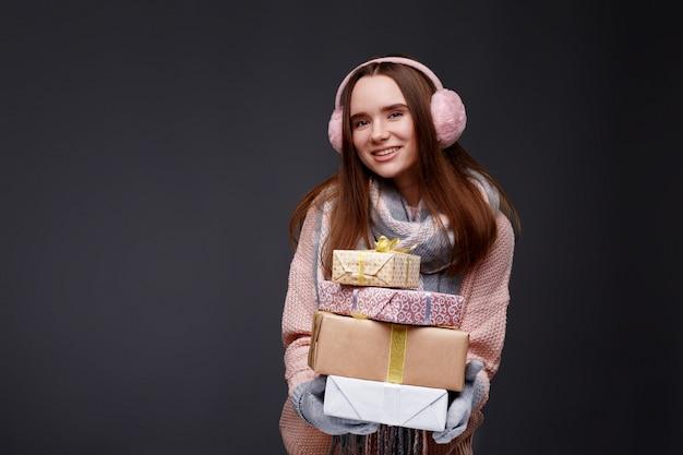 Jeune belle fille souriante en pull à tricoter et cache-oreilles moelleux roses tenant des boîtes-cadeaux
