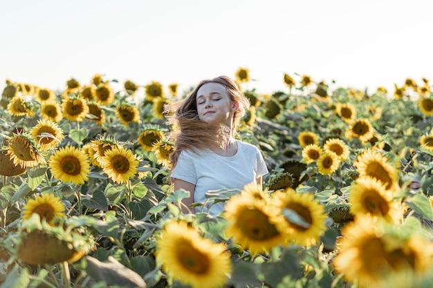 Jeune belle fille souriante et s'amuser dans un champ de tournesol par une belle journée d'été.