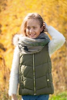 Jeune belle fille sourire le jour de l'automne