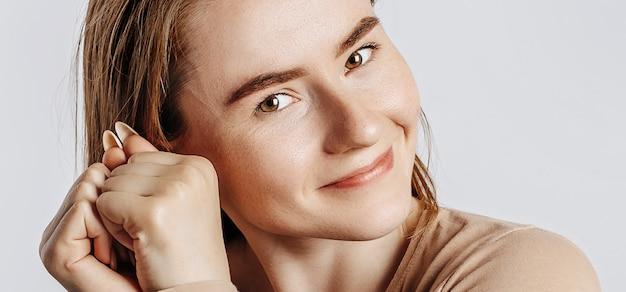 Jeune belle fille sourit et est touchée et tient deux mains au visage sur un fond blanc isolé.