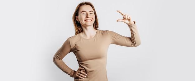 Jeune belle fille sourit et montre une mesure de petite taille avec son geste de la main sur un fond blanc isolé. une femme pointe vers une idée, un endroit pour faire de la publicité. brune positive dans un pull beige.