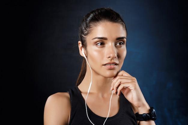 Jeune belle fille sportive écoute de la musique sur un mur sombre.