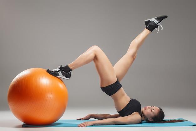 La jeune, belle fille sportive, faire des exercices sur un fitball
