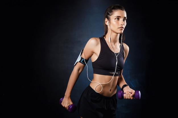 Jeune belle fille sportive s'entraînant avec des haltères sur un mur sombre.