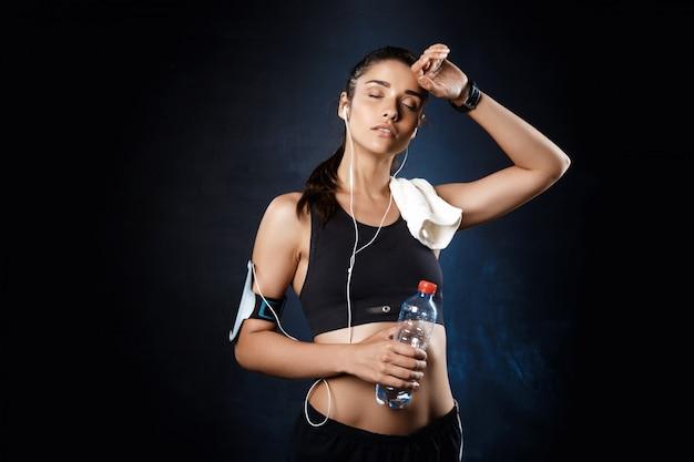 Jeune belle fille sportive tenant de l'eau sur le mur sombre.
