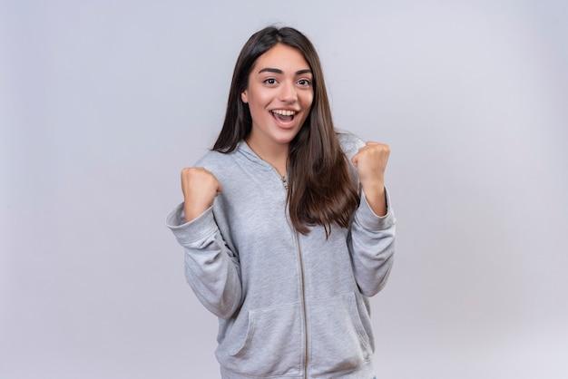Jeune belle fille en sweat à capuche gris regardant la caméra se réjouissant de son succès et de sa victoire heureuse et sortie debout sur fond blanc
