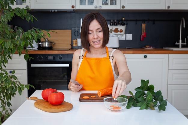 Jeune belle fille en tablier assis à table, cuisiner à la maison, hacher les légumes carottes au couteau sur une planche à découper en bois, fond de cuisine, espace copie.