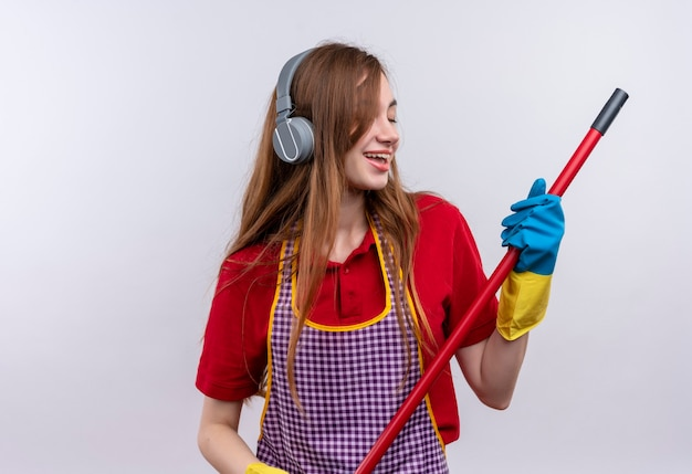 Jeune belle fille en tablier et gants en caoutchouc avec des écouteurs sur la tête tenant une vadrouille appréciant sa musique préférée