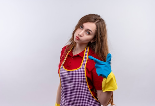Jeune belle fille en tablier et gants en caoutchouc regardant la caméra avec une expression de confiance sérieuse sur le visage pointant avec l'index sur le côté