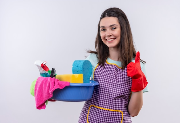 Jeune belle fille en tablier et gants en caoutchouc tenant le bassin avec des outils de nettoyage souriant avec visage heureux montrant les pouces vers le haut