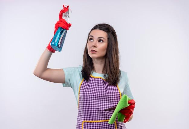 Jeune belle fille en tablier et gants en caoutchouc tenant un spray de nettoyage et un tapis va nettoyer à la confiance