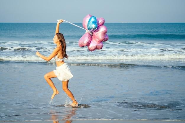 Jeune et belle fille tenant des ballons d'hélium dans l'air, courant et sautant de joie à la mer. concept de vacances et de vacances.