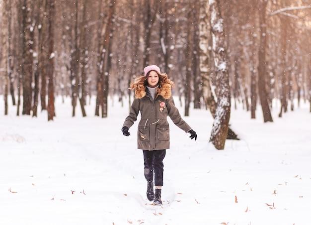 Jeune belle fille traverse la neige dans le parc en hiver