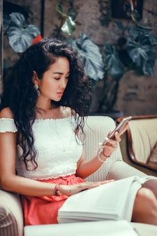 Jeune belle fille utilise un smartphone dans la rue, surfer sur internet