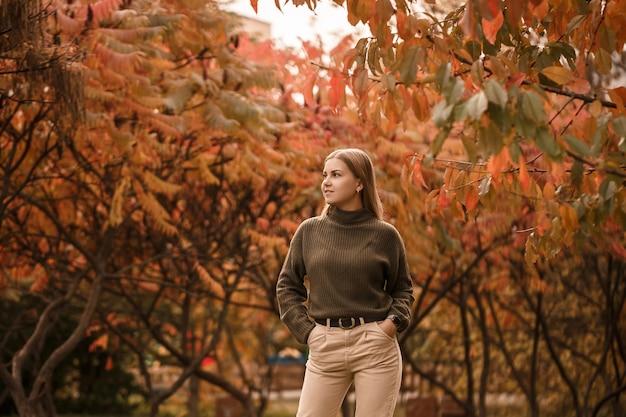 Jeune belle fille vêtue de vêtements élégants, pull vert et pantalon beige, dans un parc d'automne avec de beaux arbres