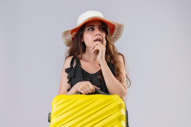 Jeune belle fille de voyageur en robe à pois en chapeau d'été tenant la valise à la position incertaine avec le doigt sur le menton avec une expression pensive pensant avoir des doutes sur le dos blanc
