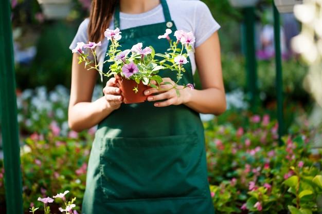 Jeune belle fleuriste posant parmi les fleurs.