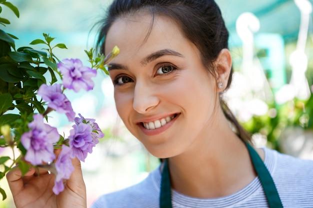 Jeune belle fleuriste posant, souriant parmi les fleurs.