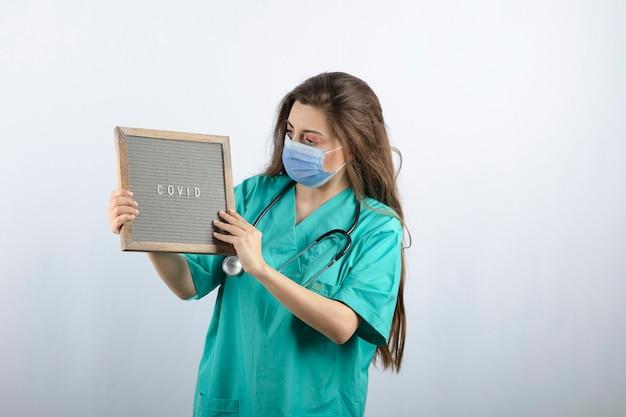 Jeune belle infirmière en masque médical avec stéthoscope tenant un cadre