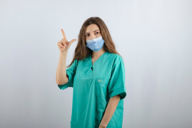 Jeune belle infirmière en uniforme vert dans un masque médical pointant vers le haut